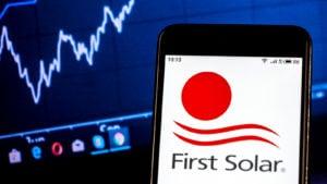 Logo First Solar (FSLR) sur smartphone devant un écran d'ordinateur avec des graphiques